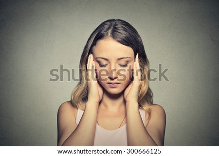Closeup portrait stressed sad young woman eyes closed hands touching head isolated on gray wall background  - stock photo