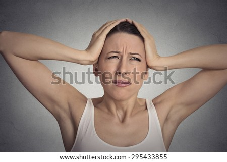 Closeup portrait stressed sad young woman overwhelmed having headache about to cry, hands on head   - stock photo