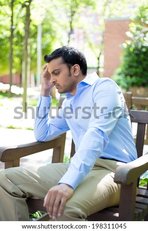 Closeup portrait, stressed young business man, hand on head, worried, isolated background of trees outside. Negative human emotion facial expression feelings. - stock photo
