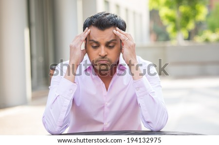 Closeup portrait, stressed young businessman, hands on head with bad headache, isolated background of trees, buildings, outside. Negative human emotion facial expression feelings. - stock photo