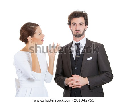 Closeup portrait stressed young couple going through hard times in relationship, isolated white background. Upset angry wife, girlfriend gesturing if her husband is an idiot, man feels guilty, annoyed - stock photo