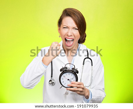 Closeup portrait stressed young female doctor, health care professional, nurse holding alarm clock, very unhappy, screaming, demanding, pressured by time, isolated green background. Negative emotions - stock photo