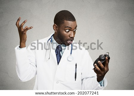 Closeup portrait stressed young male doctor, health care professional nurse holding alarm clock, very unhappy, shocked, demanding pressured by time isolated black background. Negative emotion reaction - stock photo