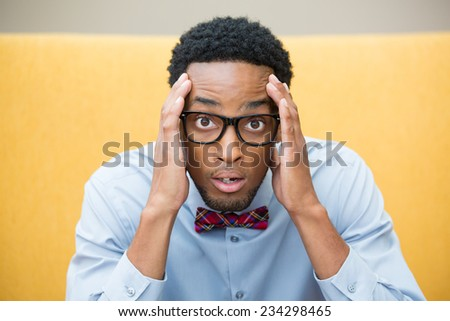 Closeup portrait, stunned nerd young man, hands on head, open mouth jaw drop with bow tie and big glasses, isolated yellow background. Negative human emotion facial expression feelings - stock photo