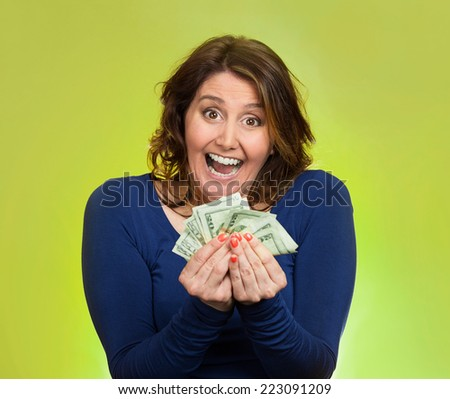 Closeup portrait super happy excited successful middle aged business woman holding money dollar bills in hand isolated green background. Positive emotion facial expression feeling. Financial reward - stock photo