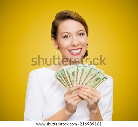 Closeup portrait super happy excited successful young business woman holding money dollar bills in hand, isolated yellow background. Positive emotion facial expression feeling. Financial reward - stock photo