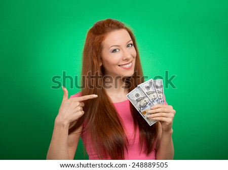 Closeup portrait super happy excited successful young business woman holding money dollar bills in hand isolated on green background. Positive emotion facial expression feeling. Financial reward