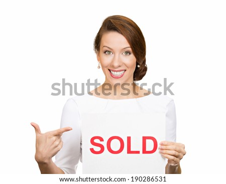 Closeup portrait, super happy excited successful young business woman holding, pointing to red sold sign, isolated white background. Positive emotion feeling. Financial reward - stock photo