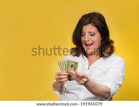 Closeup portrait super happy excited successful young woman holding money dollar bills in hand isolated yellow background. Positive emotion facial expression feeling reaction. Financial reward savings