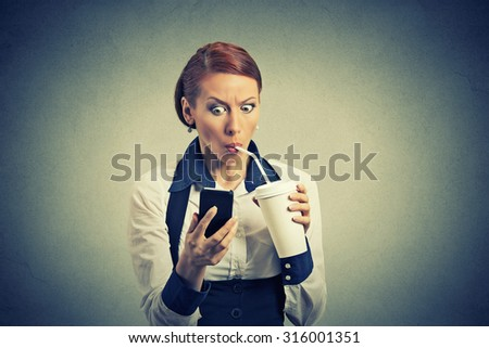 Closeup portrait surprised business woman reading breaking news on smart phone drinking soda coffee isolated on grey wall background. Human face expression, corporate executive emotions - stock photo