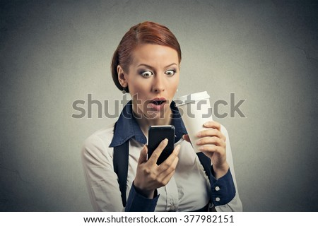 Closeup portrait surprised business woman reading news on smart phone drinking soda coffee isolated on gray background. Human face expression emotion. Attractive girl browsing website on cell phone - stock photo