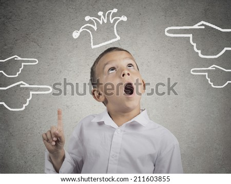 Closeup portrait surprised young man looking up with wide open mouth isolated on grey wall background with crown above his head and someone's pointed hands. Human face expression emotion body language - stock photo