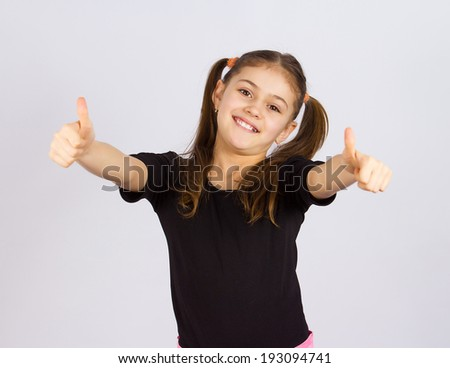 Closeup portrait sweet little, happy, smiling, relaxed excited girl giving thumbs up, isolated  grey background. Childhood, positive emotion, facial expressions, reaction, attitude, life perception - stock photo