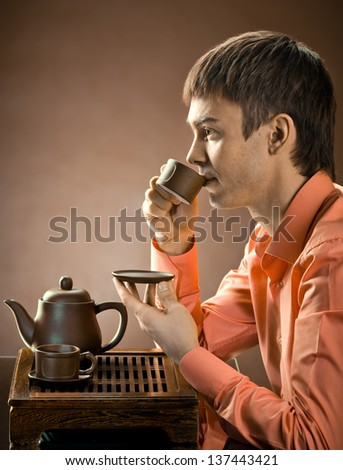 closeup portrait  the  beautiful man hold cup with green  tea,  on brown background - stock photo