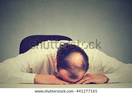 Closeup portrait, tired middle aged bald boss company employee sleeping after long working hours, resting on desk, isolated gray office wall background. Exhausting work hours