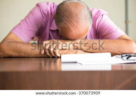 Closeup portrait, tired old bald boss sleeping after filling out so much paperwork, resting on desk, isolated indoors background. Grueling work hours, need more caffeine - stock photo