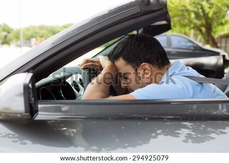 Closeup portrait tired young handsome man with short attention span, driving his car after long hours trip, trying to stay awake at wheel, isolated outside background. Sleep deprivation - stock photo