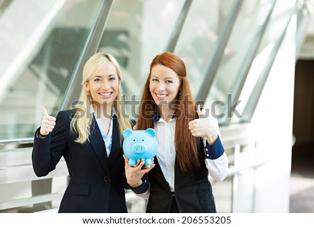 Closeup portrait two smiling business women bank employees holding piggy bank giving thumbs up isolated corporate office background. Financial savings banking concept. Positive emotion face expression - stock photo