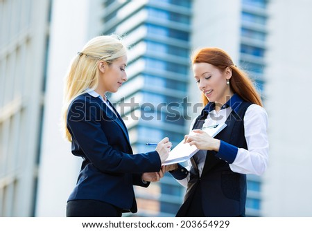 Closeup portrait two smiling young business women, company employees signing contract document, agreement paper, paperwork isolated corporate office background.