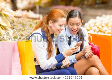 Closeup portrait two surprised girls looking at cell phone discussing latest gossip news. Young shopping women reading news on smartphone, sitting in park on a bench. Face expression body language - stock photo