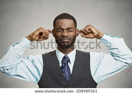 Closeup portrait unhappy, annoyed man plugging closing ears with fingers, disgusted ignoring something not wanting to hear someone side story, isolated grey background. Human emotion body language - stock photo