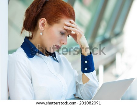 Closeup portrait unhappy business woman, hand on head standing, bothered by mistake, reading email, bad news on computer having headache isolated background corporate office. Negative face expression - stock photo