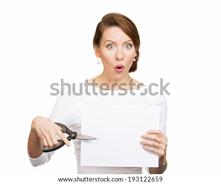 Closeup portrait, unhappy, confused, surprised, shocked business woman, funny looking female, worker employee cutting blank white paper, copy space, scissors isolated white background. Face expression - stock photo