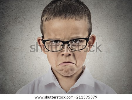 Closeup portrait unhappy, sad, child, funny looking boy in white shirt, with glasses isolated grey wall background. Negative human emotions, facial expressions, feelings, life perception, reaction - stock photo