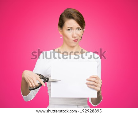 Closeup portrait, unhappy, skeptical, confused, displeased business woman, funny female, worker, employee cutting blank white paper, copy space, scissors isolated pink background. Facial expressions - stock photo