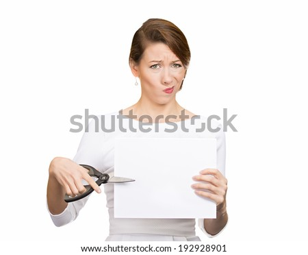 Closeup portrait, unhappy, skeptical, confused, displeased business woman, funny female, worker, employee cutting blank white paper, copy space, scissors isolated white background. Facial expressions - stock photo