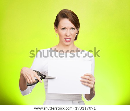 Closeup portrait, unhappy, skeptical, confused, displeased business woman, funny female, worker, employee cutting blank white paper, copy space, scissors isolated green background. Facial expressions - stock photo