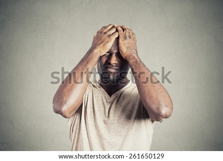 Closeup portrait unhappy upset guy, sad young man bothered by mistakes hands on head eyes closed isolated on grey wall  background. Negative emotion face expression  - stock photo