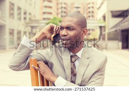 Closeup portrait unhappy upset sad, skeptical man talking on phone sitting outdoors isolated office background. Negative human emotion facial expression feeling, life reaction. Bad news - stock photo