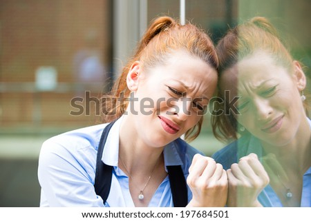 Closeup portrait unhappy young business woman, head on window, bothered by mistake having bad headache isolated background corporate office. Negative human emotion, facial expression life reaction - stock photo