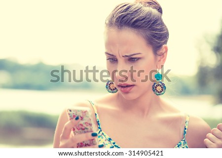 Closeup portrait upset sad skeptical unhappy serious woman talking texting on phone displeased with conversation isolated outdoors park background. Negative human emotion face expression feeling - stock photo