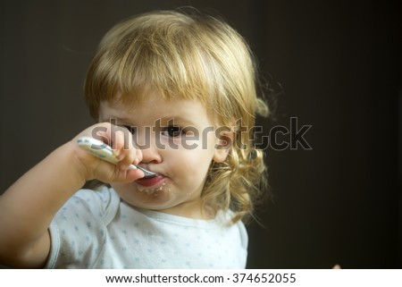 Closeup portrait view of one adorable cute small baby boy with blonde hair eating healthy food of porridge or coocked semolina with spoon in hand indoor, horizontal picture - stock photo