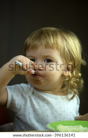 Closeup portrait view of one adorable cute small baby boy with blonde hair eating healthy food of porridge or coocked semolina from plate with spoon in hand indoor, vertical picture - stock photo