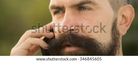 Closeup portrait view of one handsome young pensive man with long dark haired beard speaking on mobile phone outdoor on blurred green natural background, horizontal picture - stock photo