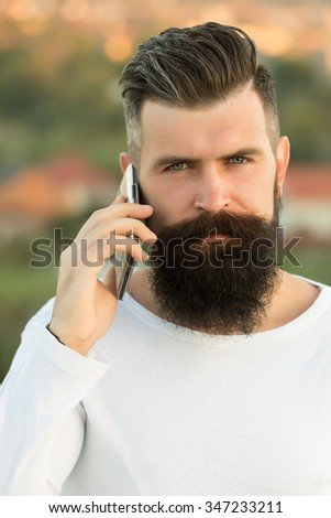 Closeup portrait view of one handsome young pensive man with long dark haired beard speaking on mobile phone outdoor on blurred natural background, vertical picture - stock photo