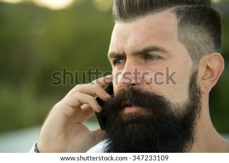 Closeup portrait view of one handsome young serious man with long dark haired beard speaking on mobile phone outdoor on blurred green natural background, horizontal picture - stock photo