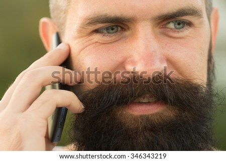 Closeup portrait view of one handsome young smiling man with long dark haired beard speaking on mobile phone outdoor on blurred green natural background, horizontal picture - stock photo