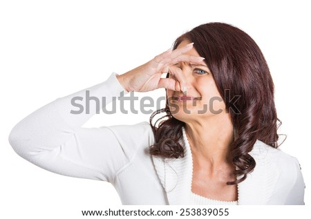 Closeup portrait woman covers her nose disgusted something stinks, very bad smell situation isolated on white background. Human face expression  - stock photo