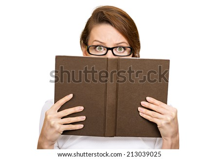 Closeup portrait woman with glasses hiding her face behind book, looking at camera suspicious, isolated white background. Education concept. Face expression, life perception. Girl holding book - stock photo