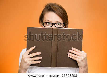 Closeup portrait woman with glasses hiding her face behind book, looking at camera suspicious, isolated orange background. Education concept. Face expression, life perception. Girl holding book - stock photo