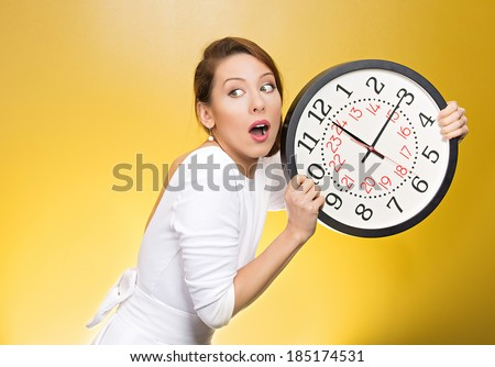 Closeup portrait woman, worker, holding clock looking anxiously, pressured by lack, running out of time, isolated yellow background. Human face expression, emotion, reaction, corporate life style - stock photo