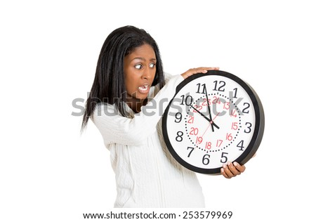 Closeup portrait woman, worker, holding clock looking anxiously, pressured by lack, running out of time isolated on white background. Human face expression emotion reaction Corporate life concept  - stock photo
