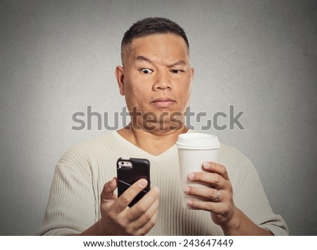 Closeup portrait worried skeptical surprised man reading bad news sms on smart mobile phone drinking holding cup coffee isolated grey wall background. Human face expression emotion  reaction - stock photo