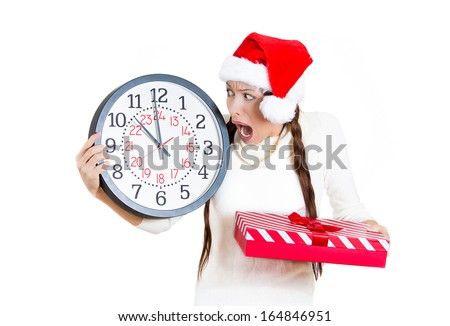Closeup portrait worried stressed in a hurry young woman wearing red santa claus hat holding clock gift box isolated white background. Emotion, funny face expression, last minute christmas shopping - stock photo