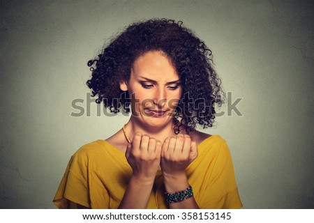 Closeup portrait worried woman looking at hands fingers nails obsessing about cleanliness isolated on grey wall background. Negative human emotion facial expression feeling body language perception - stock photo