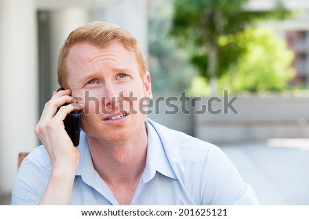 Closeup portrait, worried young man in blue shirt talking on phone to someone, looking up, isolated outdoors background - stock photo